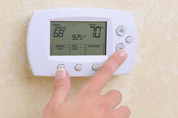 Person adjusting their residential thermostat