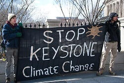 Protestors holding a sign that reads, Stop Keystone Climate Change