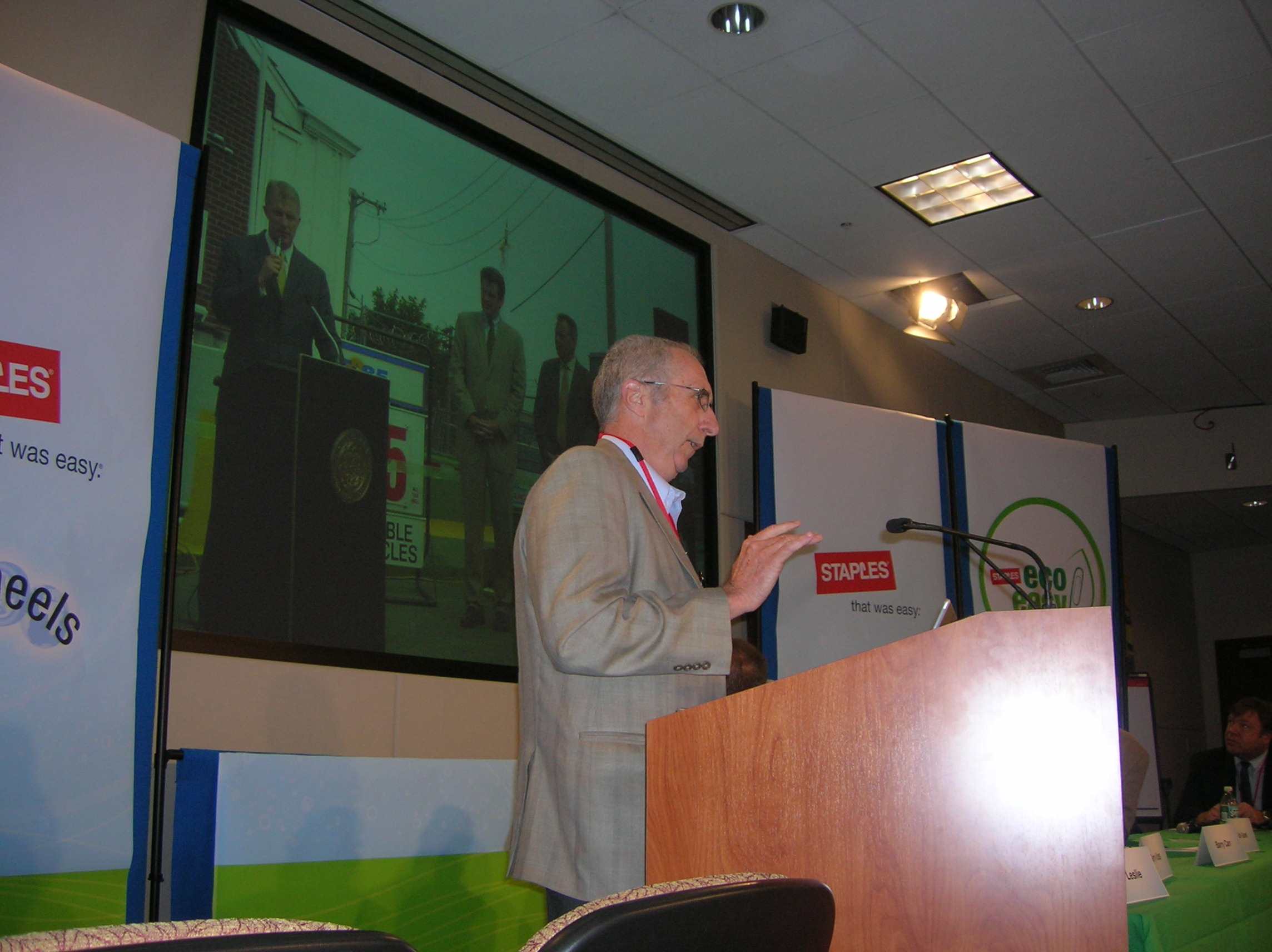 Man in a suit standing at a podium giving a speech