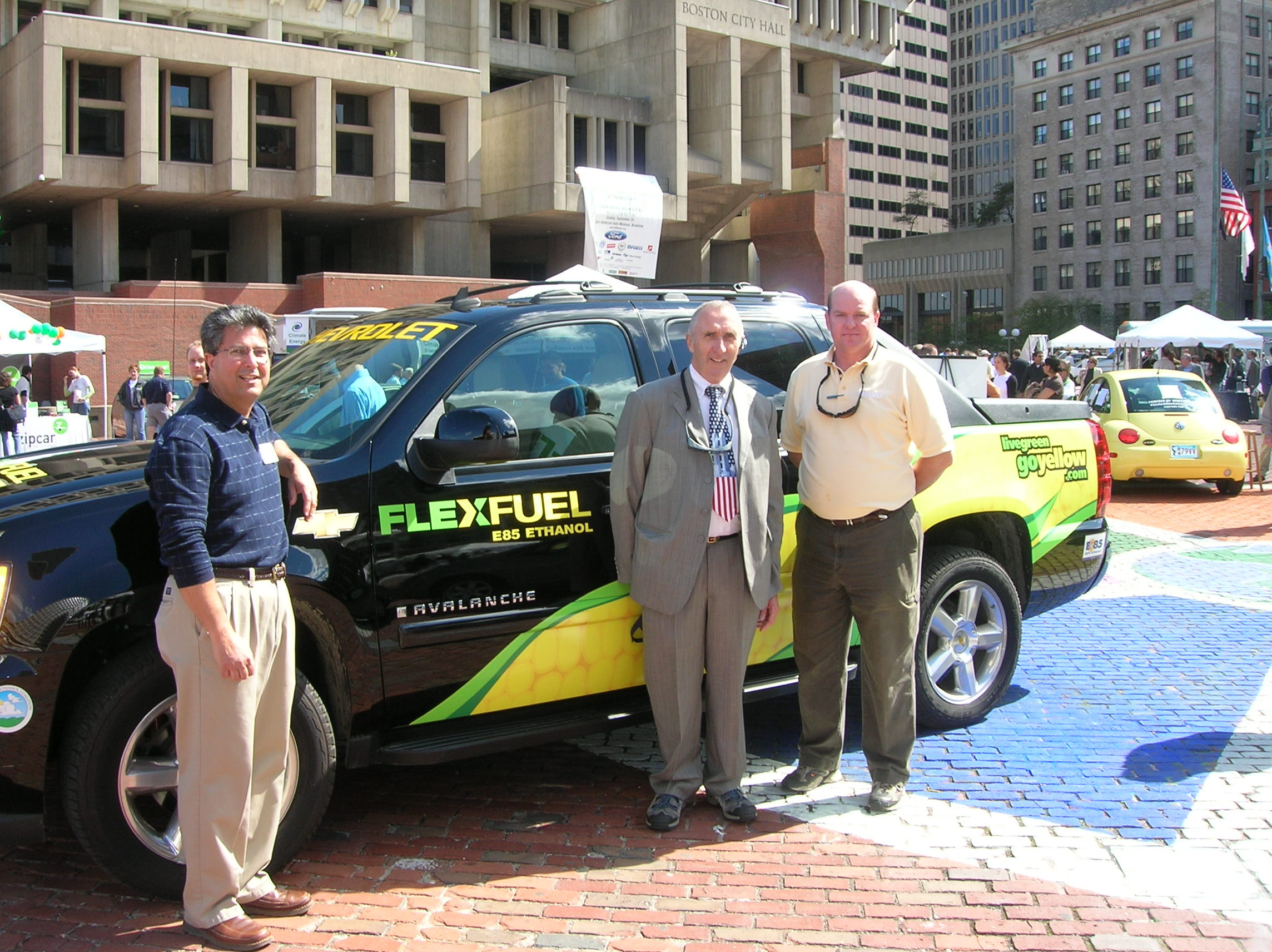 Two men standing in front of a flex fuel Chevy Avalanche