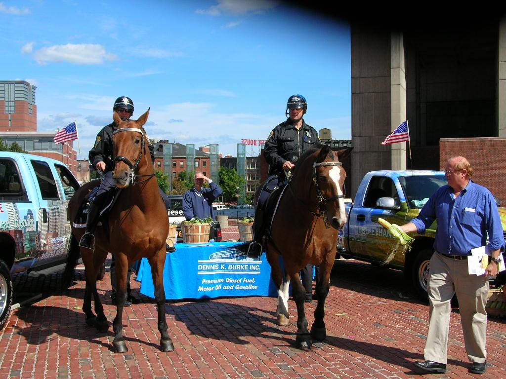 Police officers riding on horses pose infront of the Dennis K. Burke kiosk