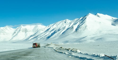 Semi-truck driving on a snowy mountain road