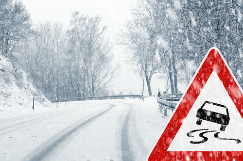 Snow covered road with a road sign showing the road is slippery