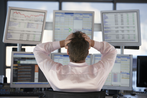 Picture of a man grasping his head looking at computer screens