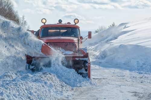Snow plow plowing a snow covered road