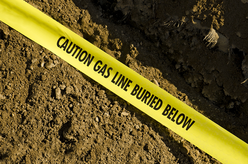 Yellow caution tape reading, caution gas line buried below