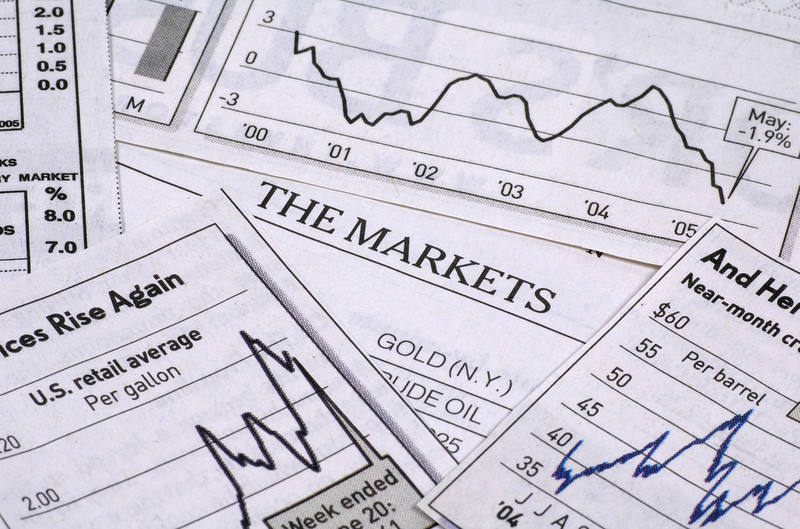 Line charts depicting the stock market scattered on a table