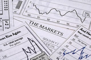 Line graphs depicting the stock market scattered over a table