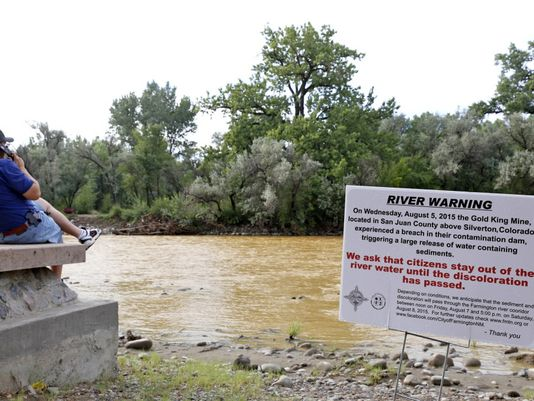 Person sitting next to a river with a river warning sign in the frame