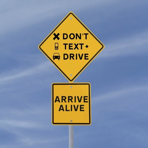 Road sign reading, Don't text and drive, arrive alive.