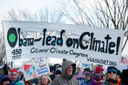 Protesters holding a sign the reads, Obama-lead onClimate