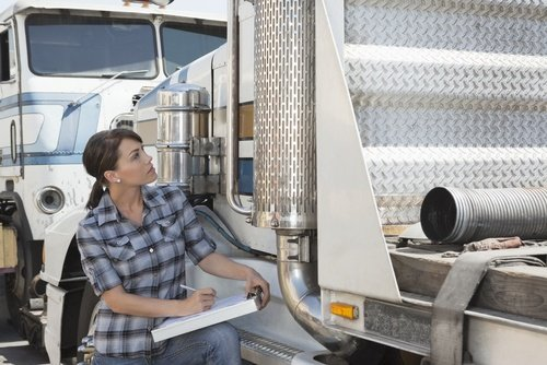 Woman performing a truck safety inspection