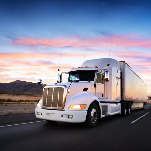 Semi-truck driving at dusk
