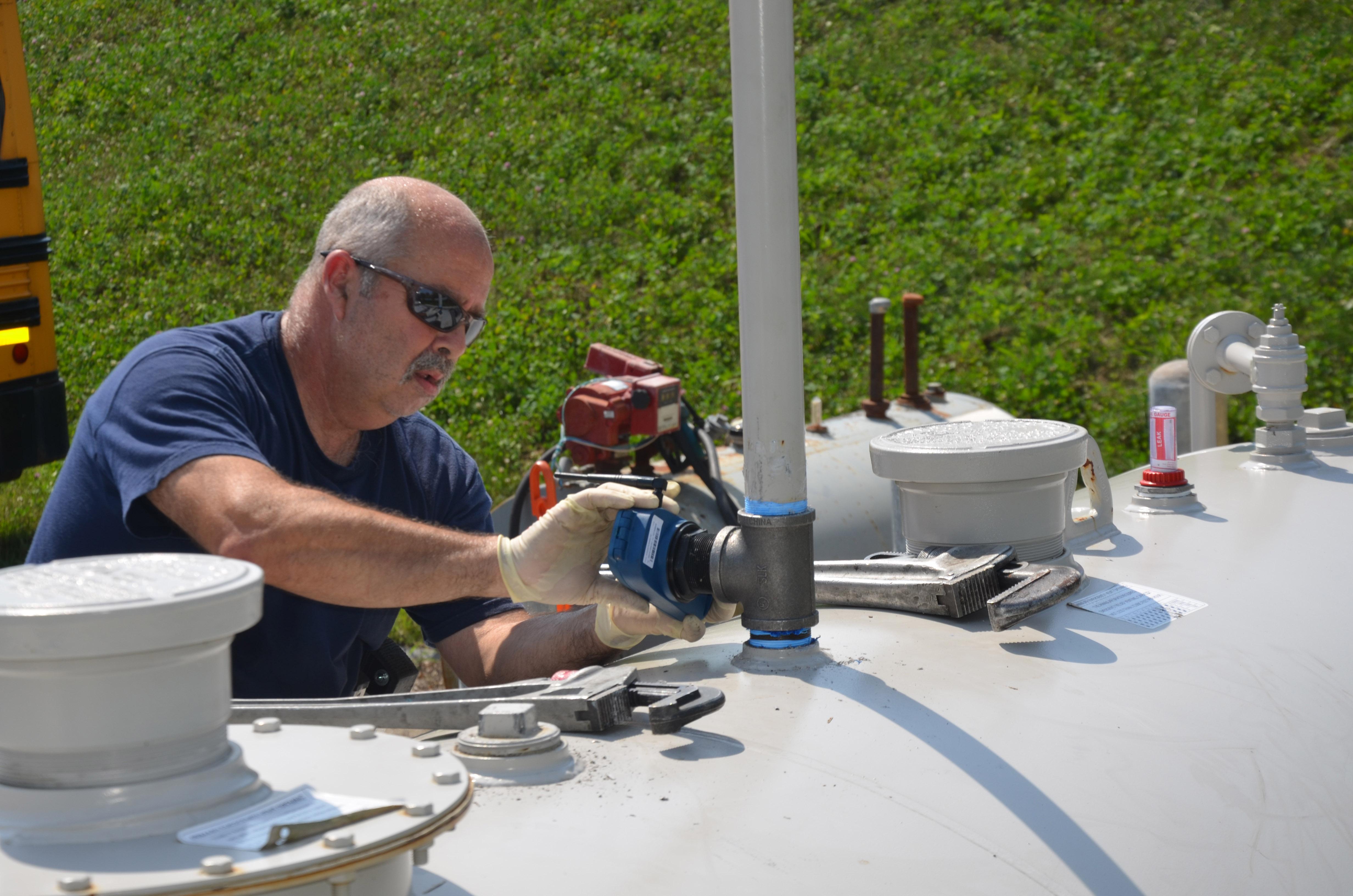 Technician installing a tank meter